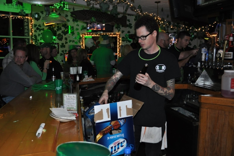 Bartender restocking the bar with beer bottles with St. Patrick's Day themed decorations in the background