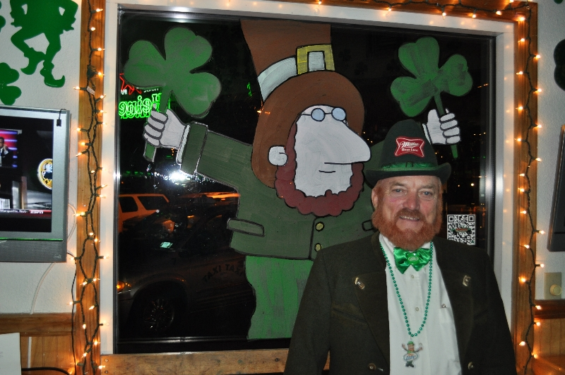 Man with a beard wearing St. Patrick's Day attire smiling standing in front of a painted leprechaun on a window