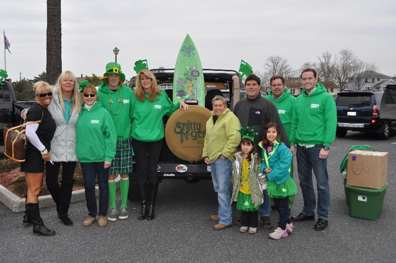 Group of friends wearing St. Patrick's Day attire standing next to the back of a Jeep