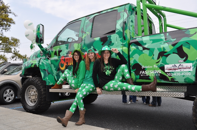 Group of friends wearing St. Patrick's Day attire sitting on a side-step of a pickup truck