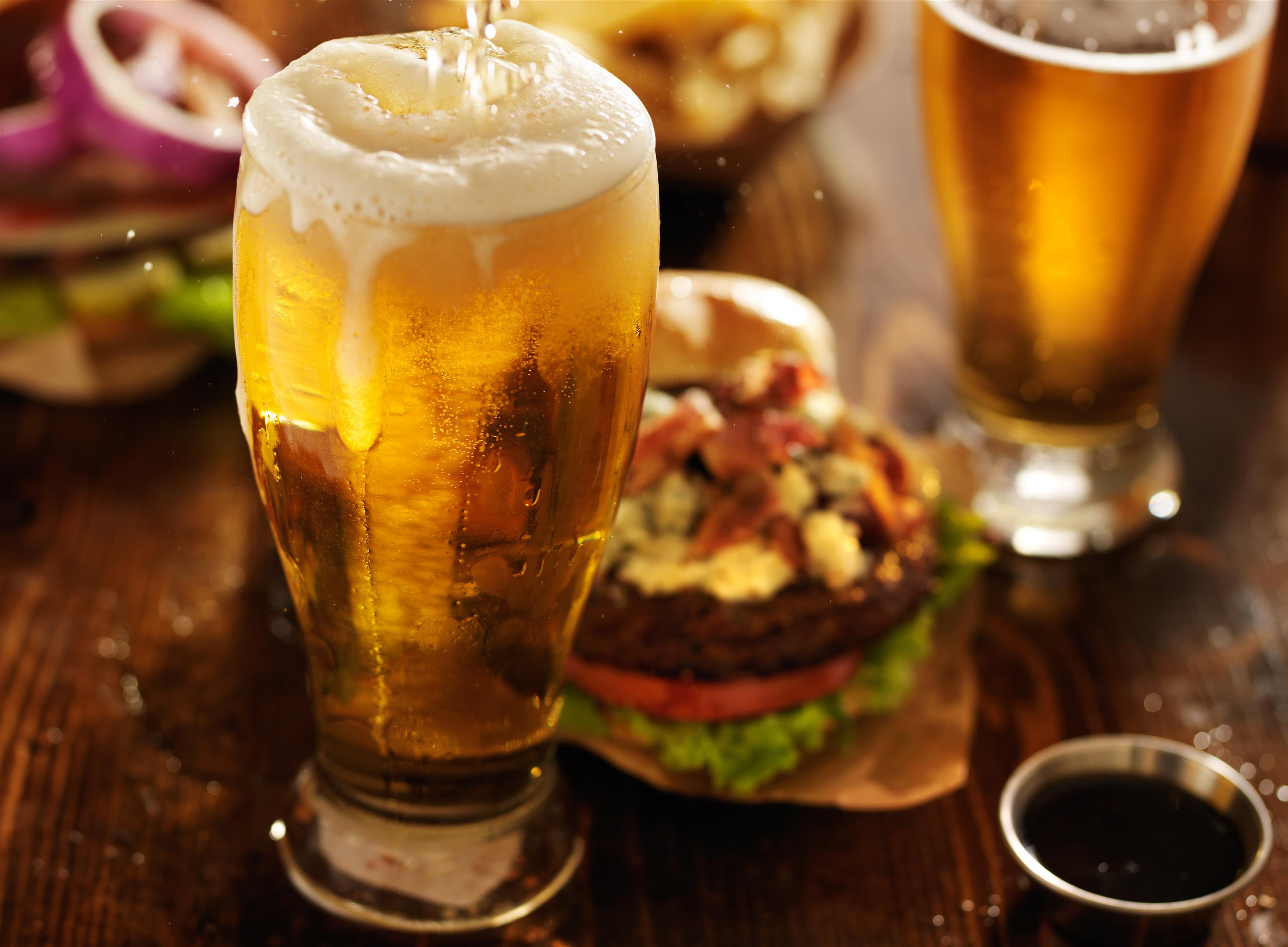 Beer being poured into a pint glass with a bacon cheese burger and a pint of beer blurred in the background