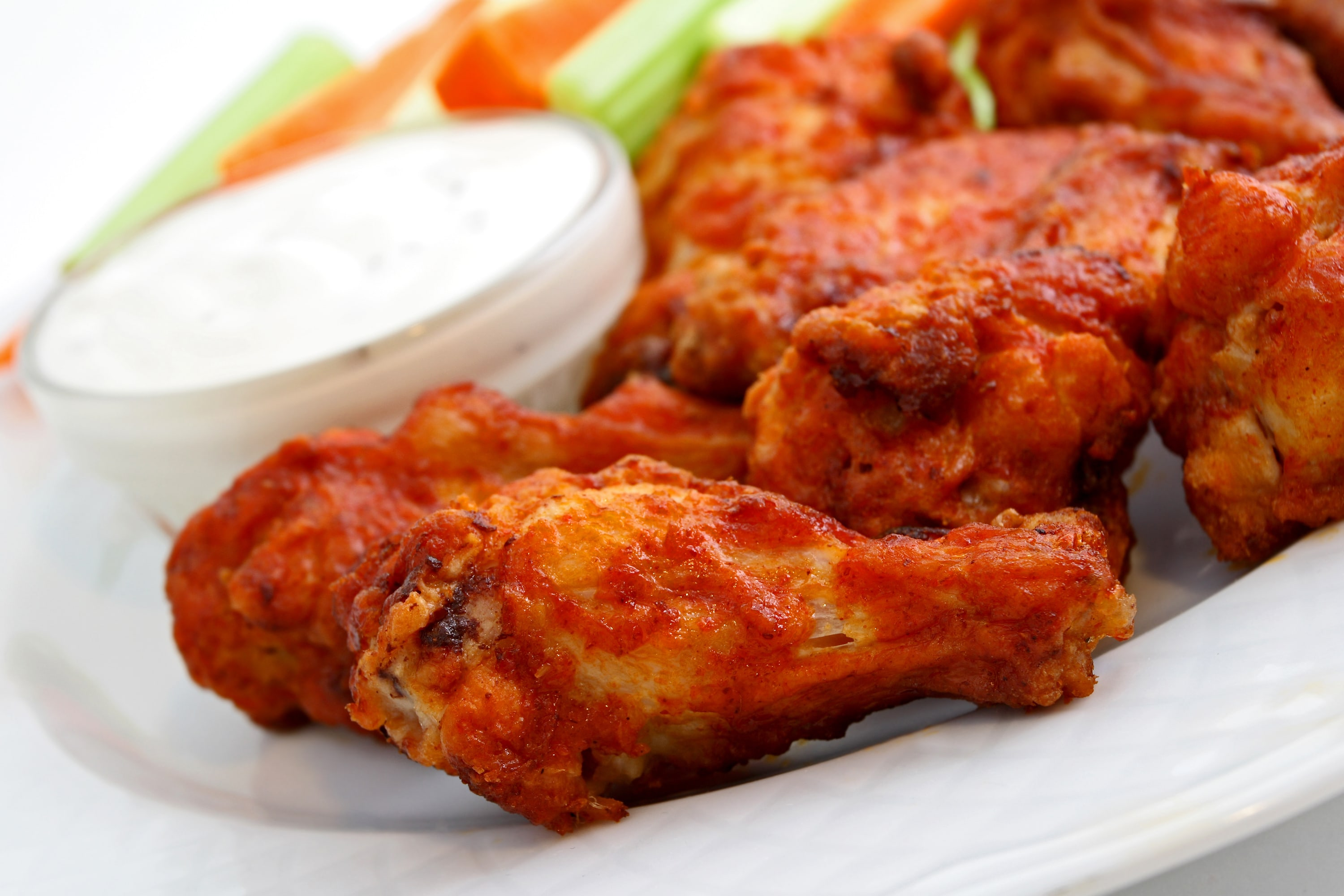 Buffalo chicken wings on a plate with bleu cheese, celery and carrots