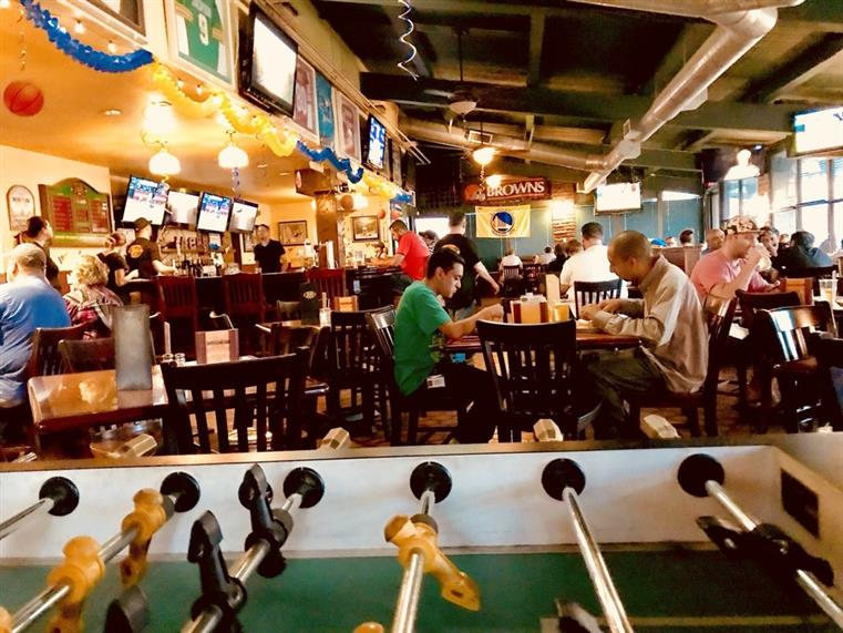 Interior bar area with wooden chairs and tables, TV's and football jerseys on the wall. in front is a foosball table.
