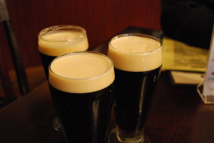 Three pints of a dark beer all with foam at the top.