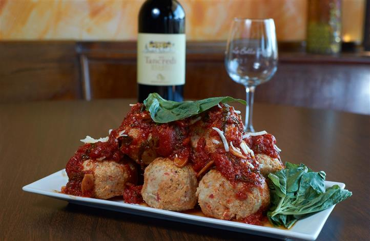 Plate of meatballs with tomato sauce and basil with a wine glass and wine bottle in the background