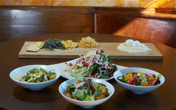 Assorted salads in bowls with a wood tray of raw pasta, flour and an egg