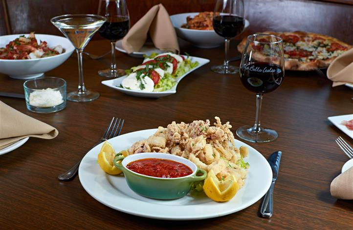 Fried calamari with marinara sauce and lemon with assorted plates of Italian food and glasses of red wine