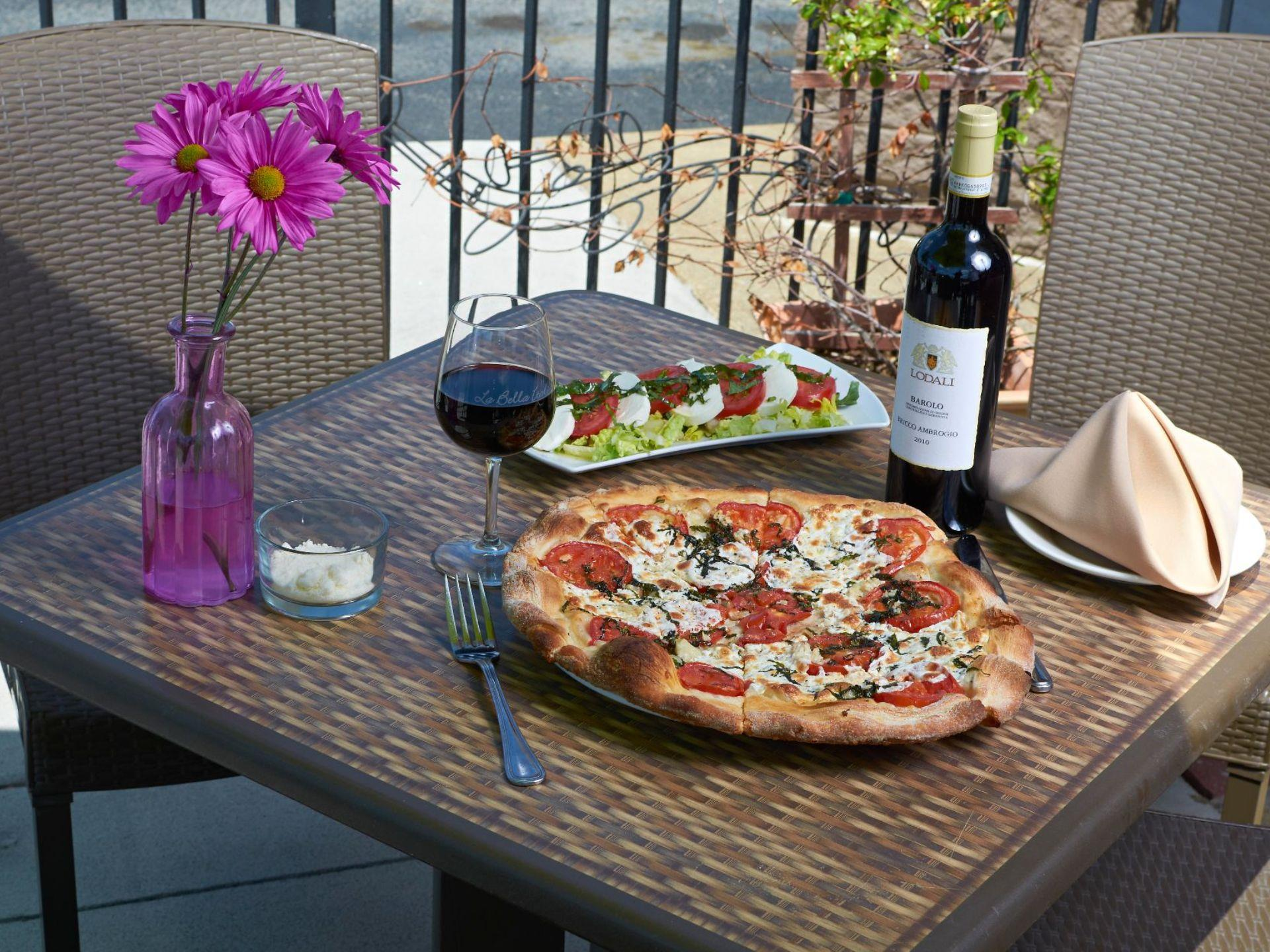 Margarita pizza on a plate with a bottle of red wine, flowers and a tomato mozzarella appetizer plate on a tabletop