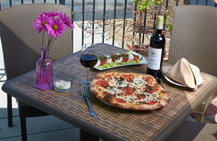 Patio table setting with a pizza and caprese salad. Bottle and glass of wine to the side. Purple flower in a purple vase.