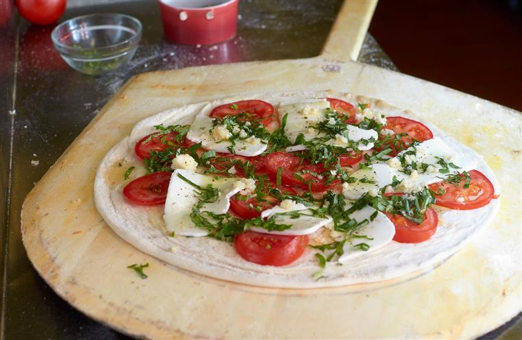 Tomato and mozzarella pizza uncooked on a wooden pizza tray