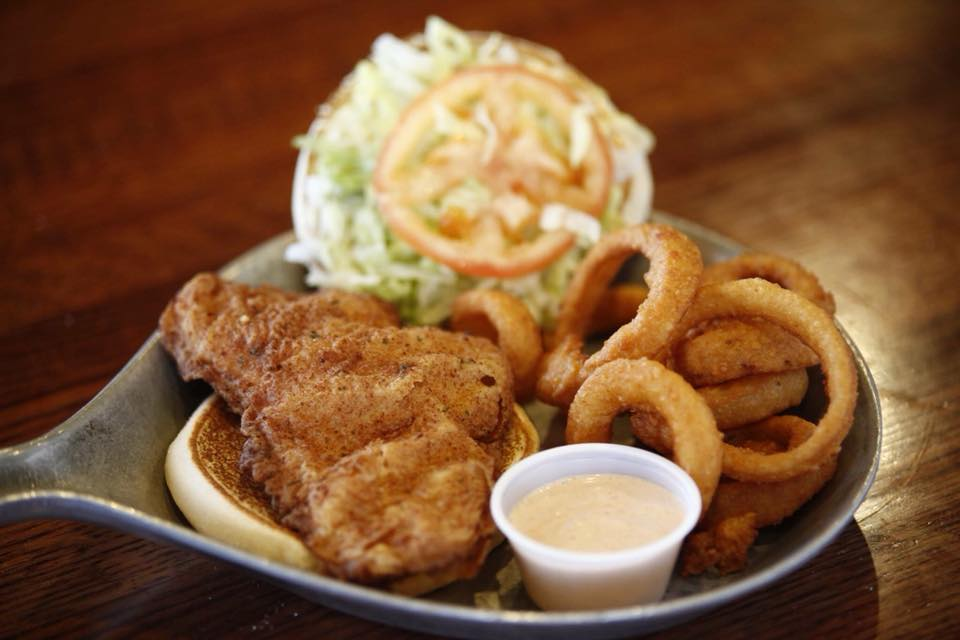 Fried fish filet with lettuce and tomato on a bun with onion rings and dipping sauce