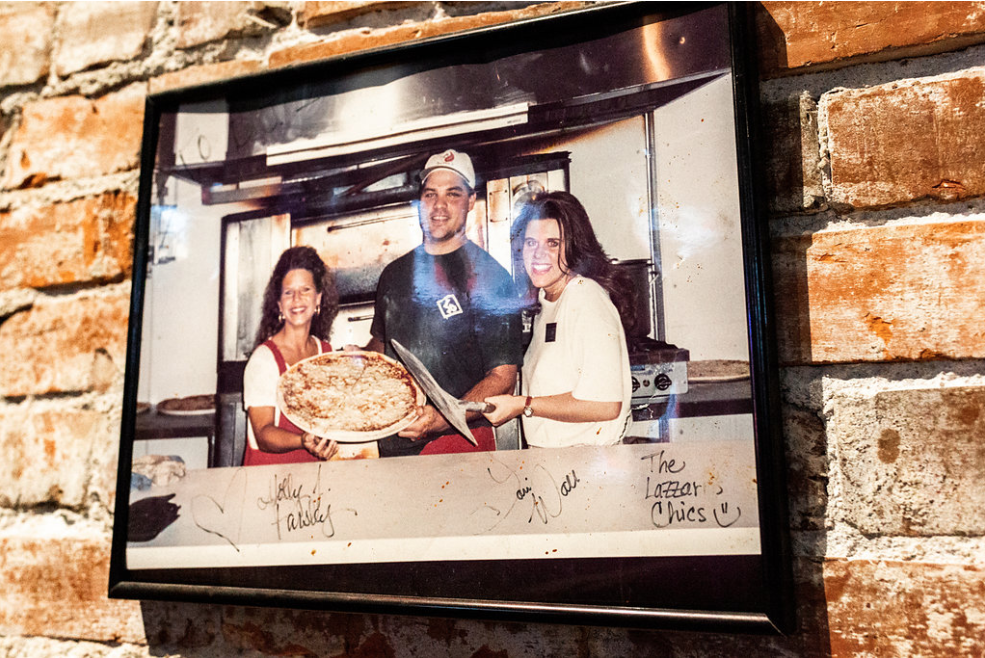 Picture frame on a brick wall of a chef holding a cooked cheese pizza standing between two women in front of a pizza oven