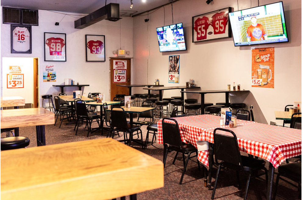 Interior dining area with tables and chairs set up with TV's and assorted sports jerseys hanging on the wall