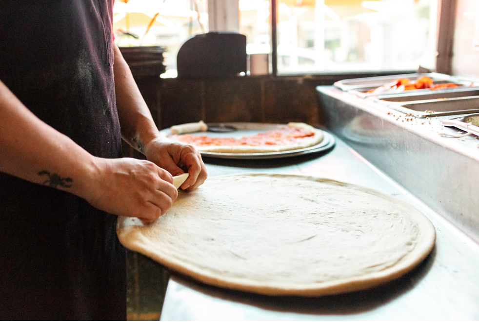 Chef preparing pizza dough with a cooked pizza blurred in the background