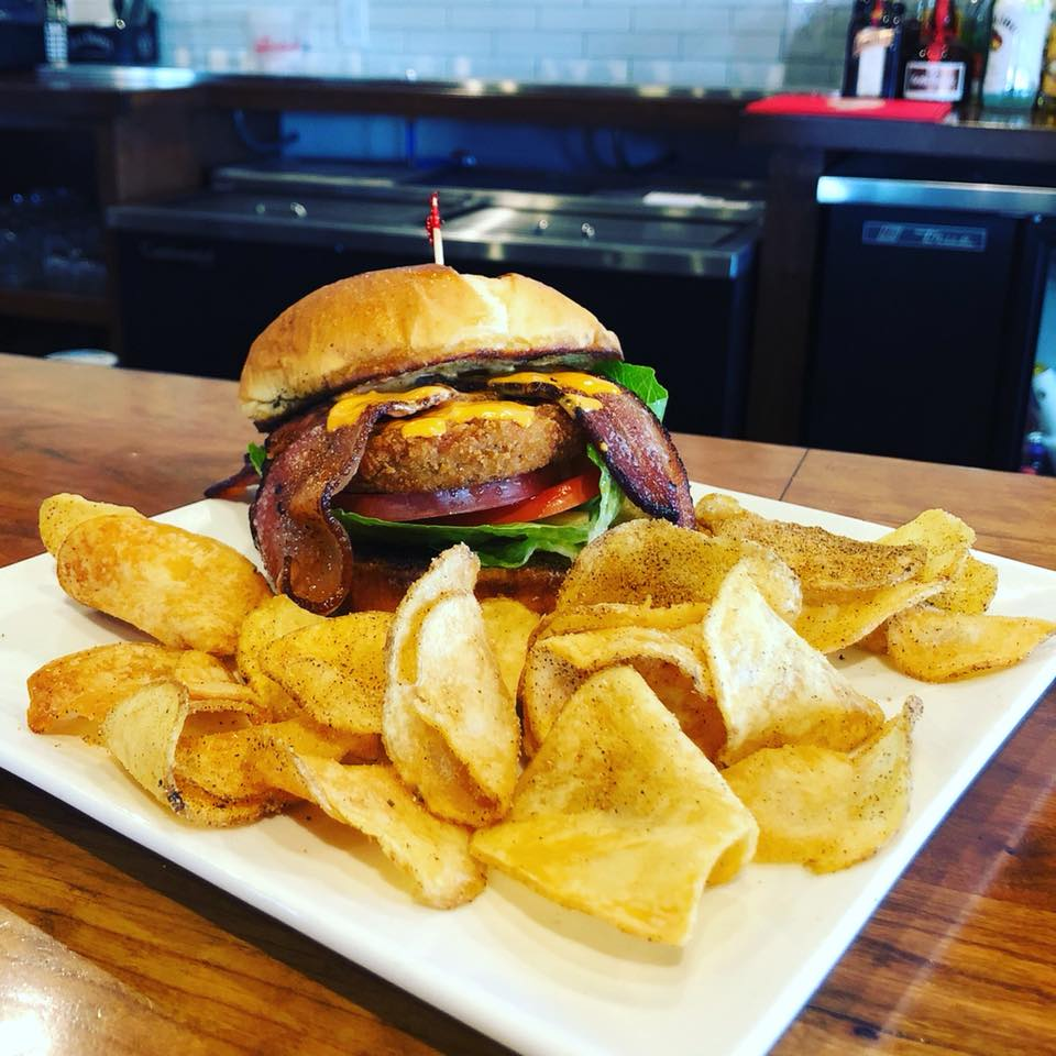 Burger with lettuce, tomato, onion, bacon, with a side of chips