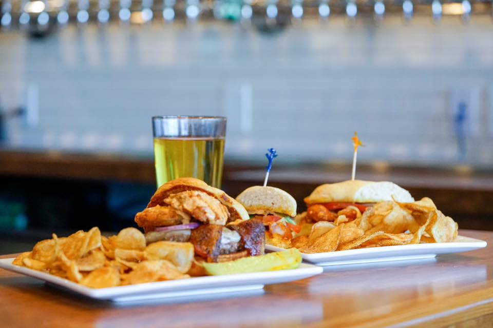 2 assorted sandwiches on plates with chips and a pickle with a beer and beer taps in the background