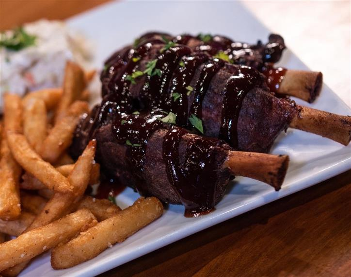 ribs topped with barbecue sauce on a plate with french fries and coleslaw on the side.
