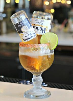 Modelo and Corona beers upside down in a margarita glass on a bar-top