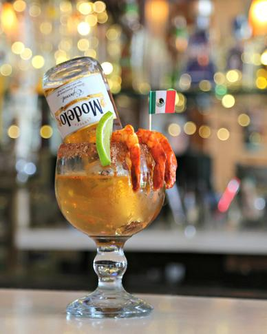 Modelo beer upside down in a margarita glass with shrimp on a bar-top