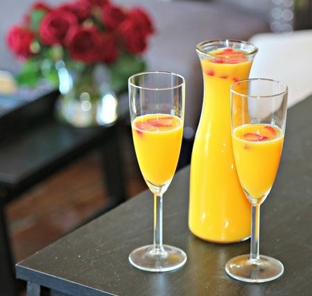 Mimosa Carafe and two champagne glasses filled with mimosa on a table