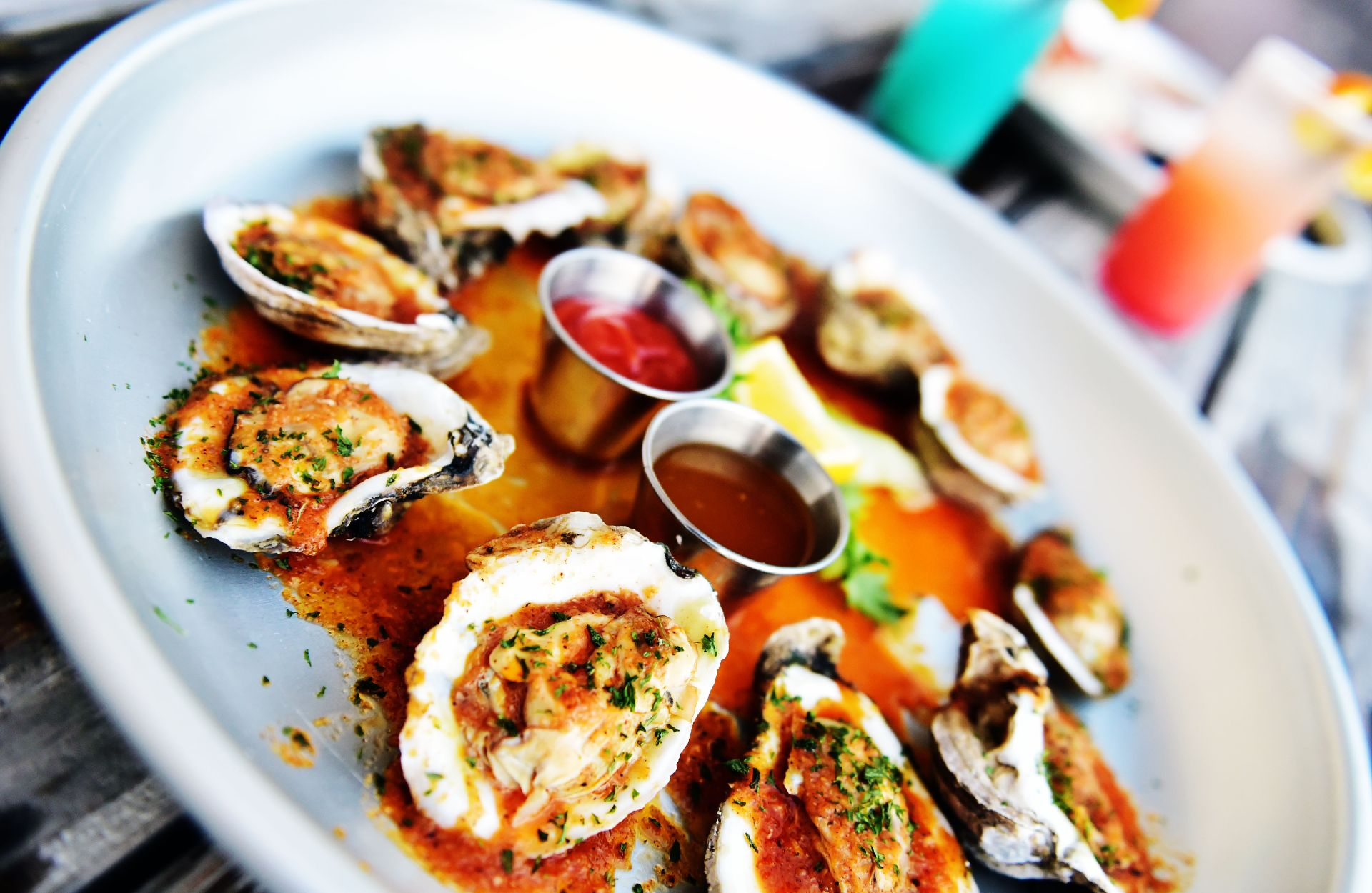 Oysters in a circular plate with sauces in the center.