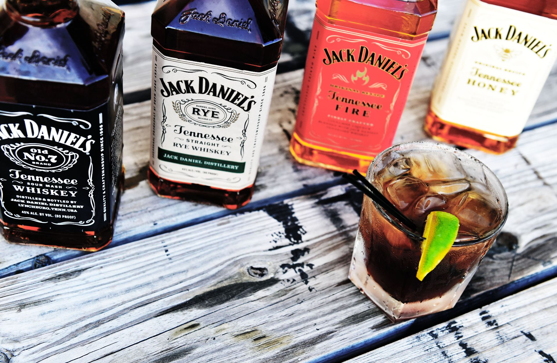 Assorted bottles of Jack Daniels with a mixed drink on a wood table