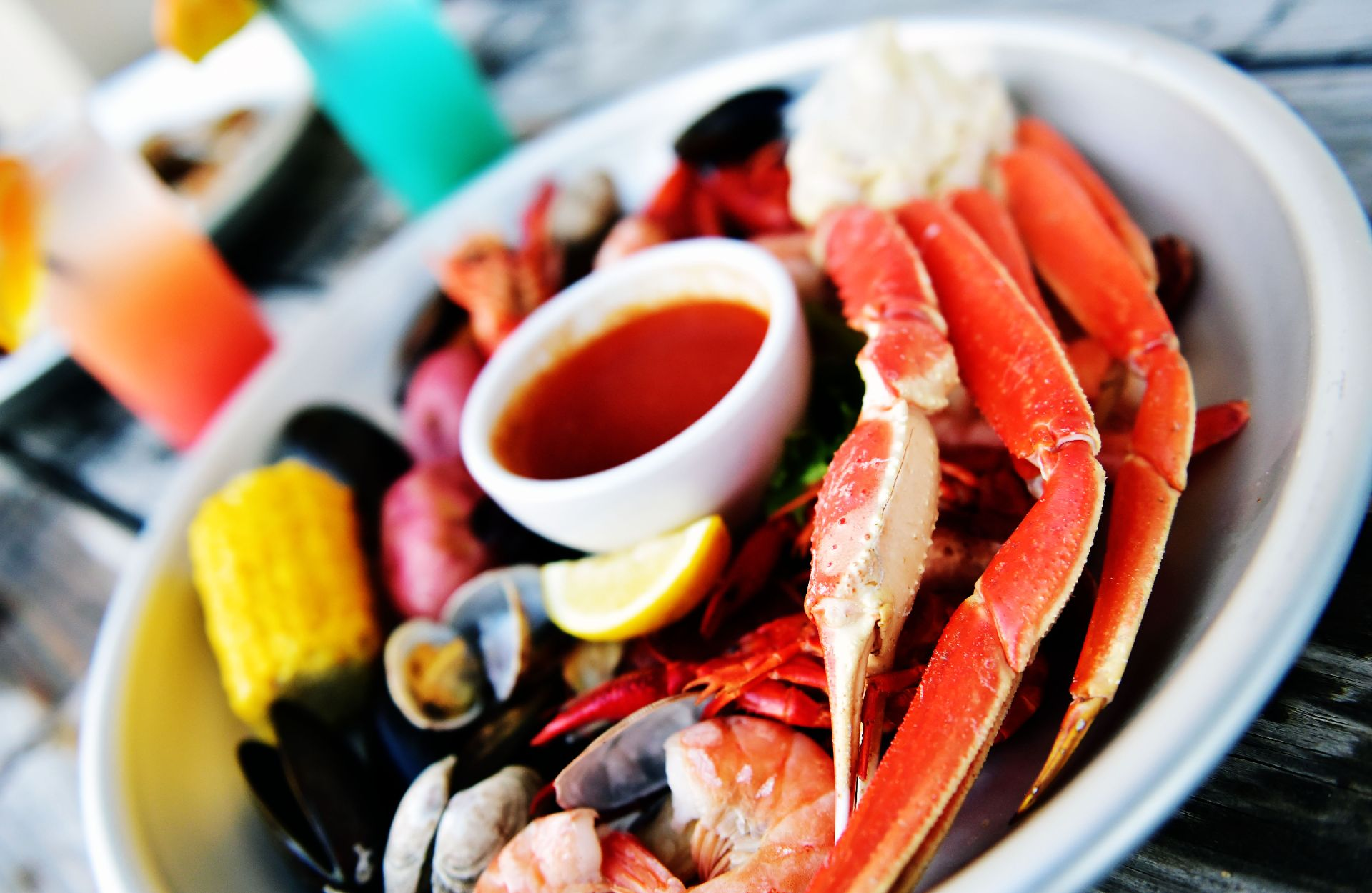 Mixed seafood boil platter with assorted cocktails on a wood background