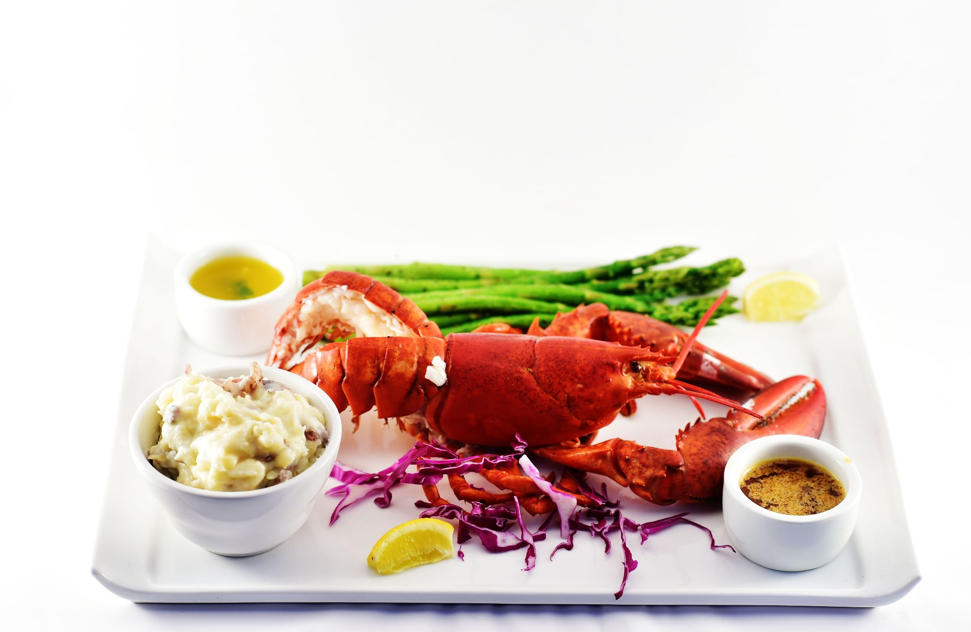 Steamed whole lobster with mashed potatoes, potatoes, red cabbage, lemon slice and asparagus