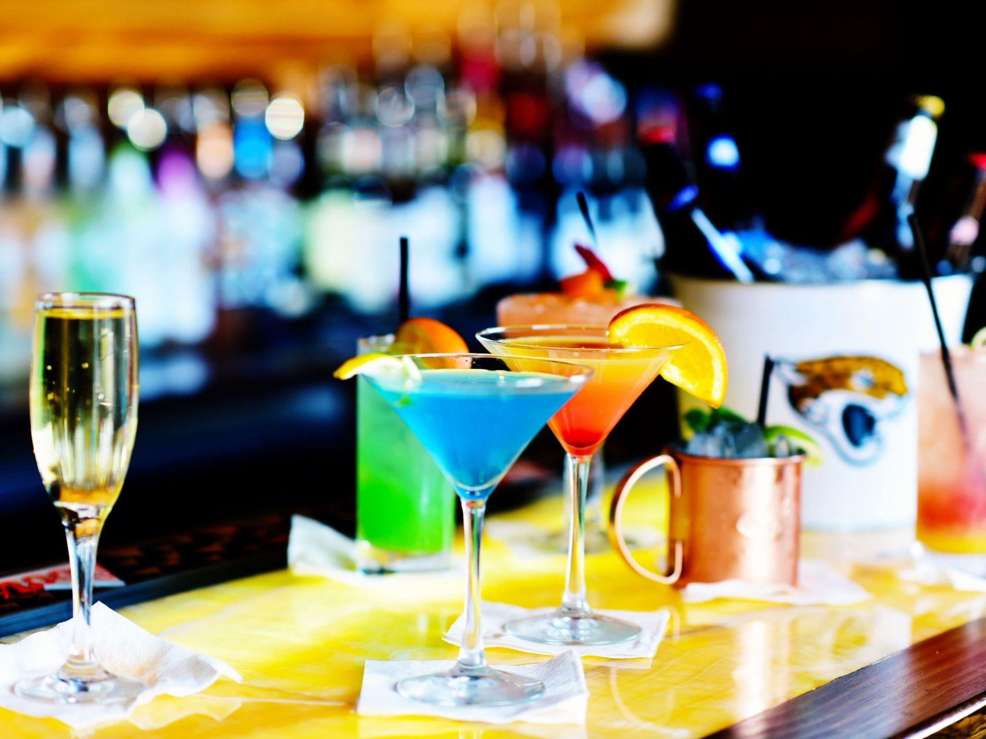 Assorted mixed cocktails on a bar-top with bottles of liquor blurred in the background