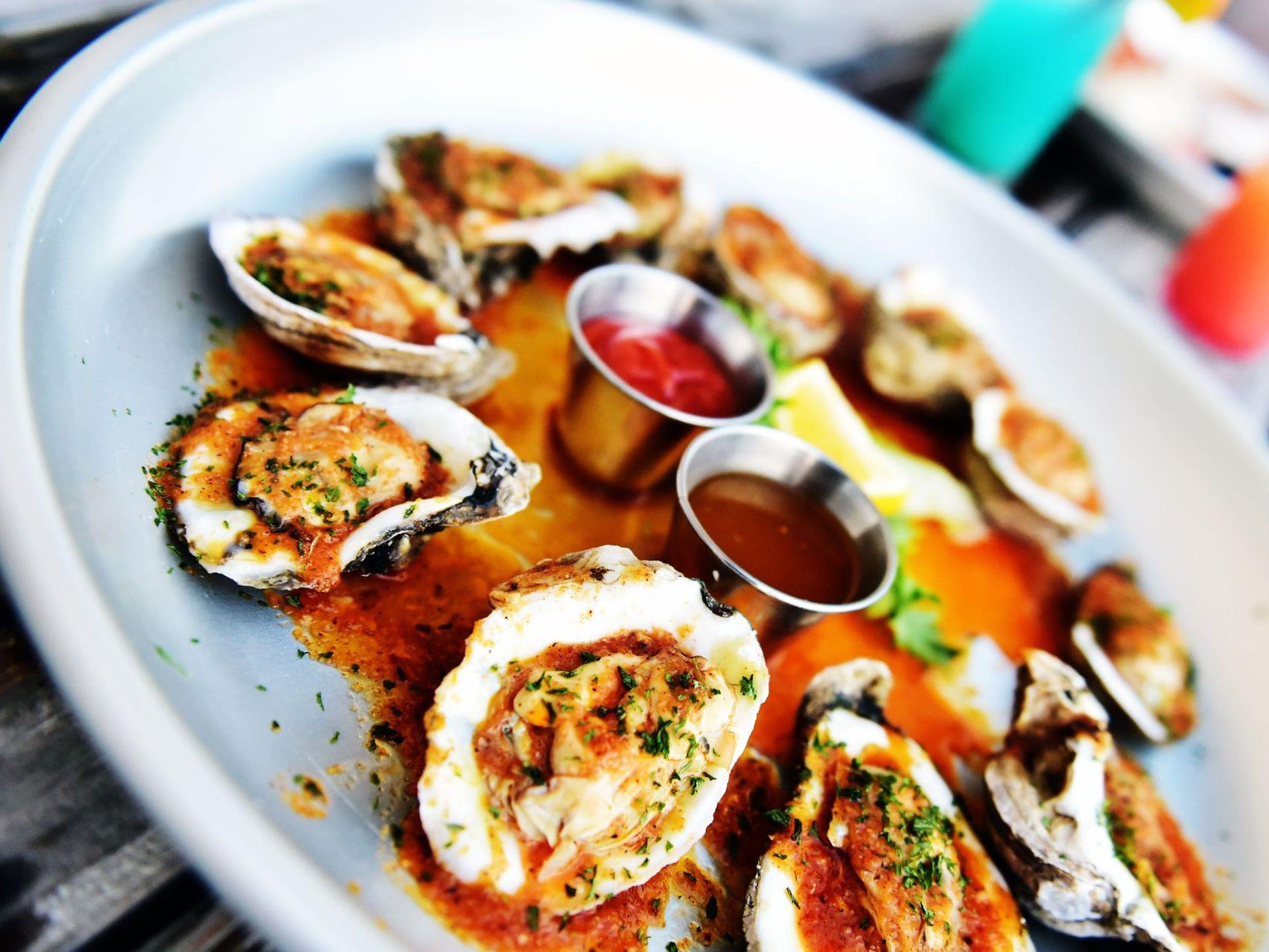 Baked oysters on the half shell on a plate with sauces in the center