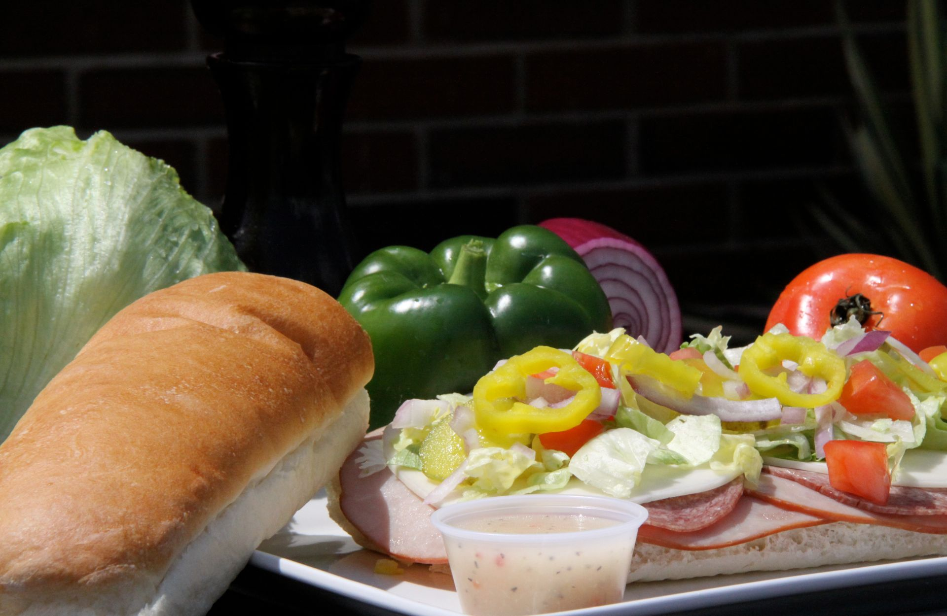 Italian sub with lettuce, tomato and banana peppers with Italian dressing, green pepper and red onion on the side