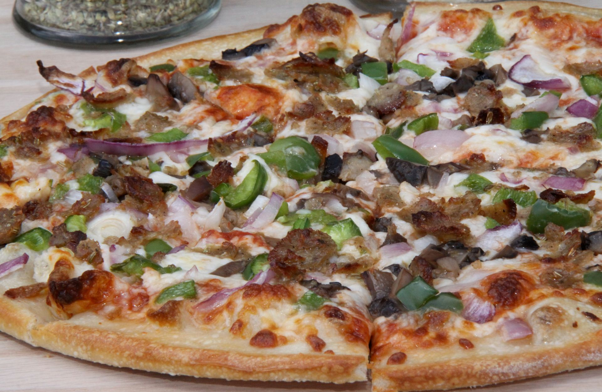 Thin crust supreme pizza with sausage, green peppers, onion and cheese