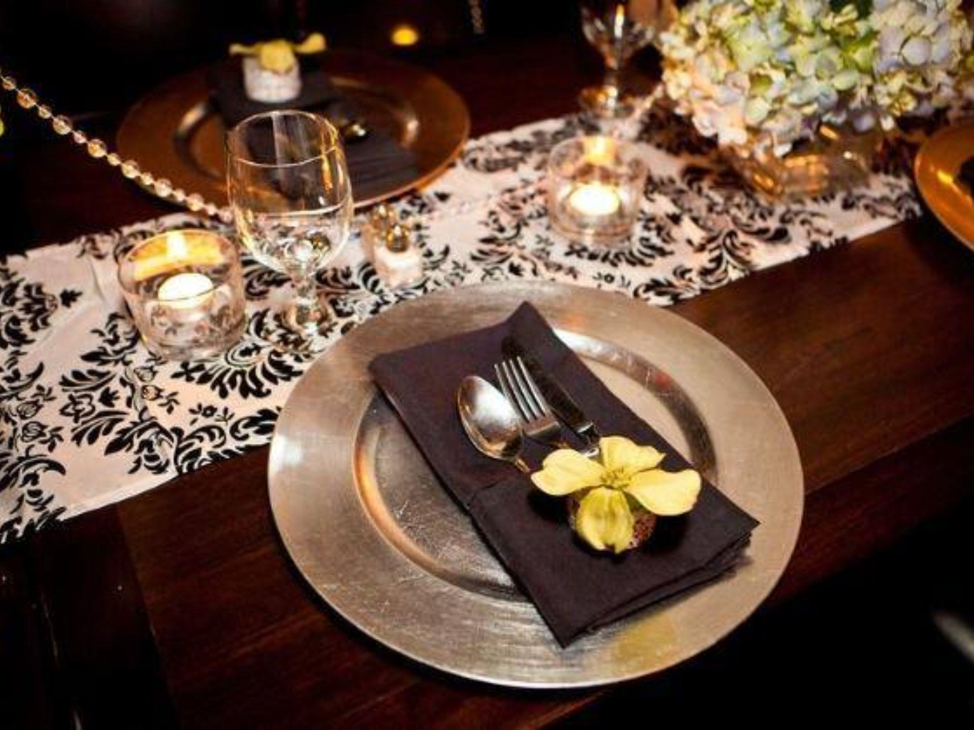 Placesetting with a fork and knife wrappe din a brown napkin with a wine glass, flowers and candles