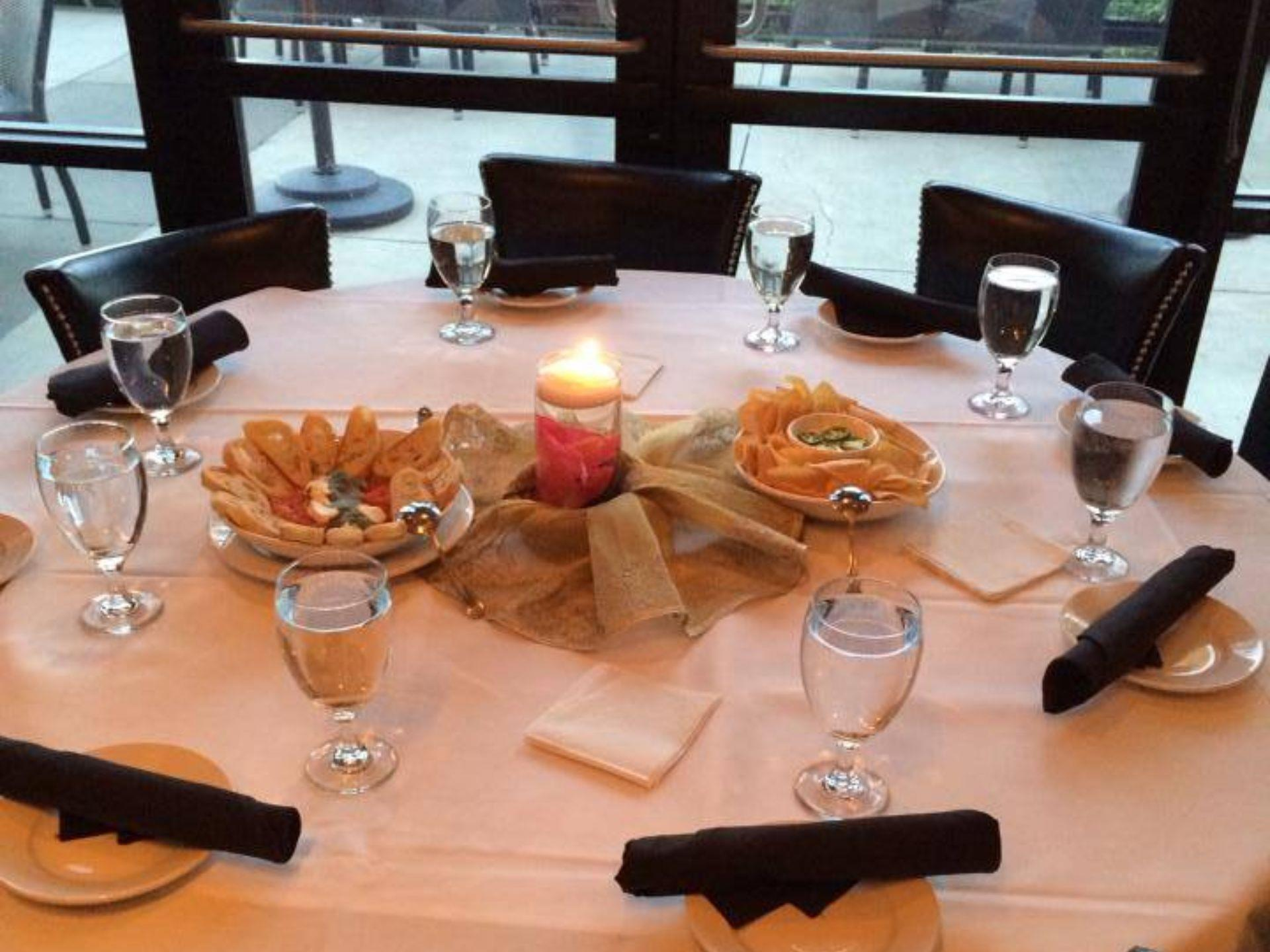 Table setting with white table cloth, a candle and assorted appetizers