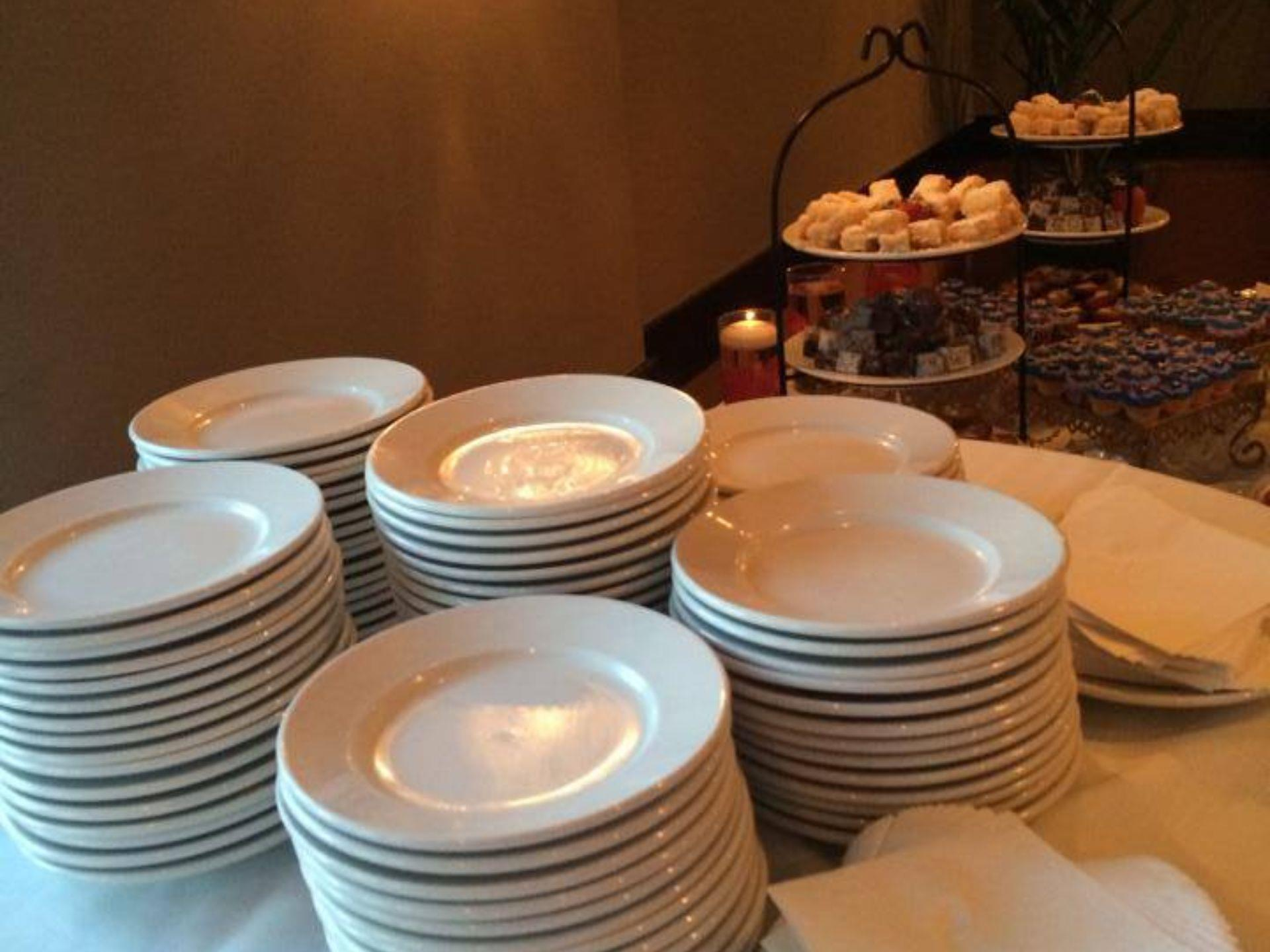Stacked white plates on a table next to a catering display