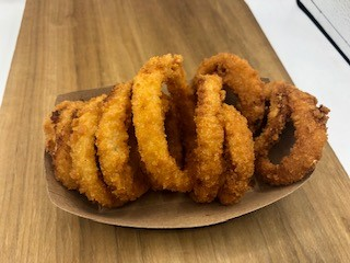basket of onion rings on a wood table.