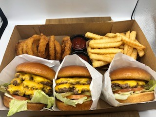 single, double, and triple cheese burger in a box to go with onion rings, french fries and ketchup.