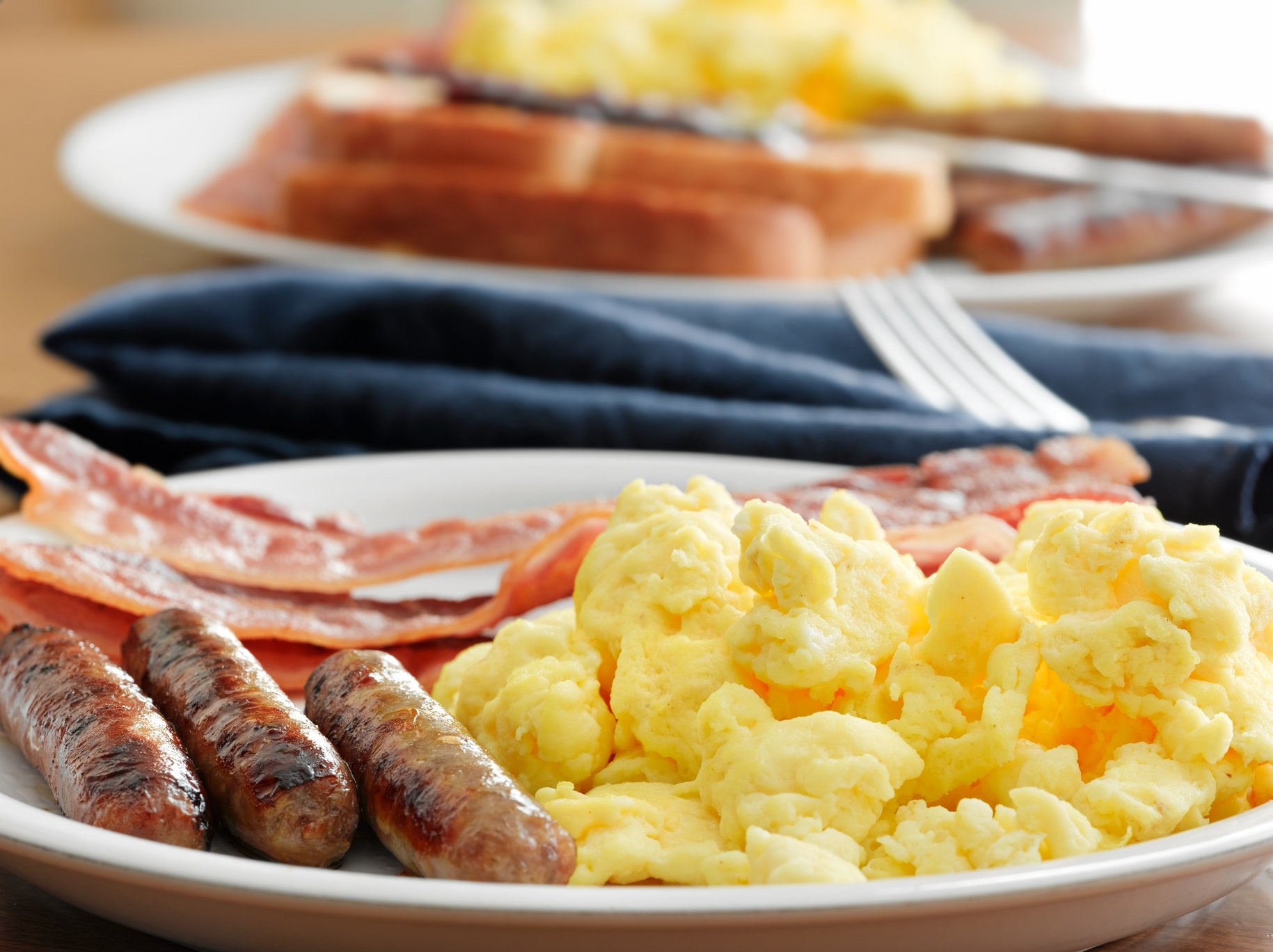 A plate of scrambled eggs, sausage and bacon with a plate blurred in the background with assorted breakfast food