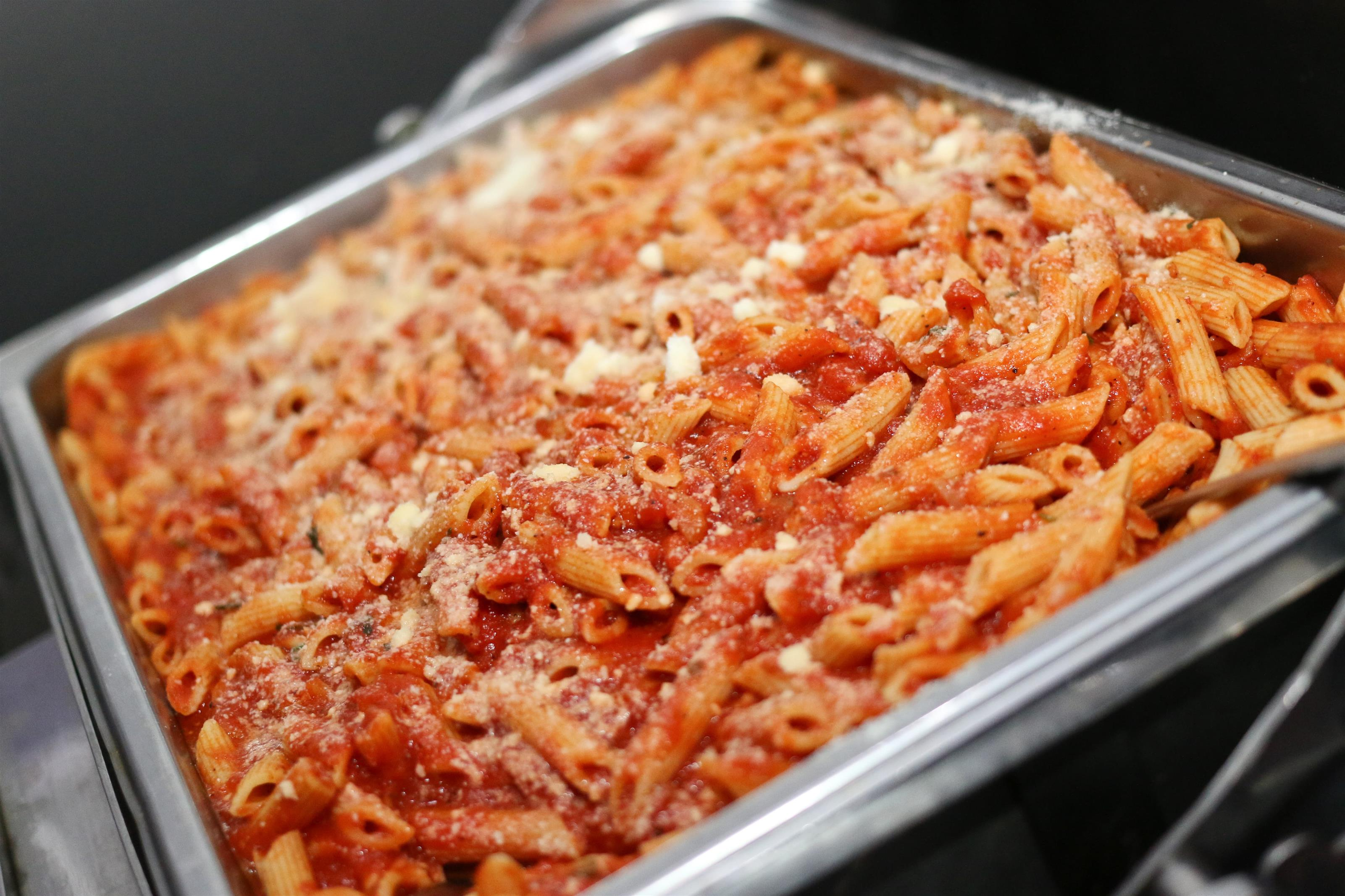 Metal tray of penne pasta and tomato sauce topped with grated cheese