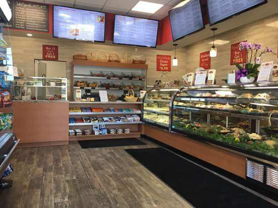 Interior shot of The Gourmet Bagel Co. of the deli display cases with assorted pre-cooked food and TV's on the wall displaying assorted daily specials