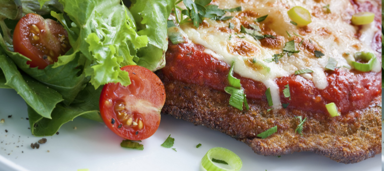Fried cutlet topped with sauce, melted cheese, parsley and green onions. On a plate next to lettuce and cherry tomatoes.