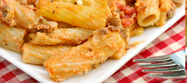 Close up of baked ziti on red and white checkered table cloth.