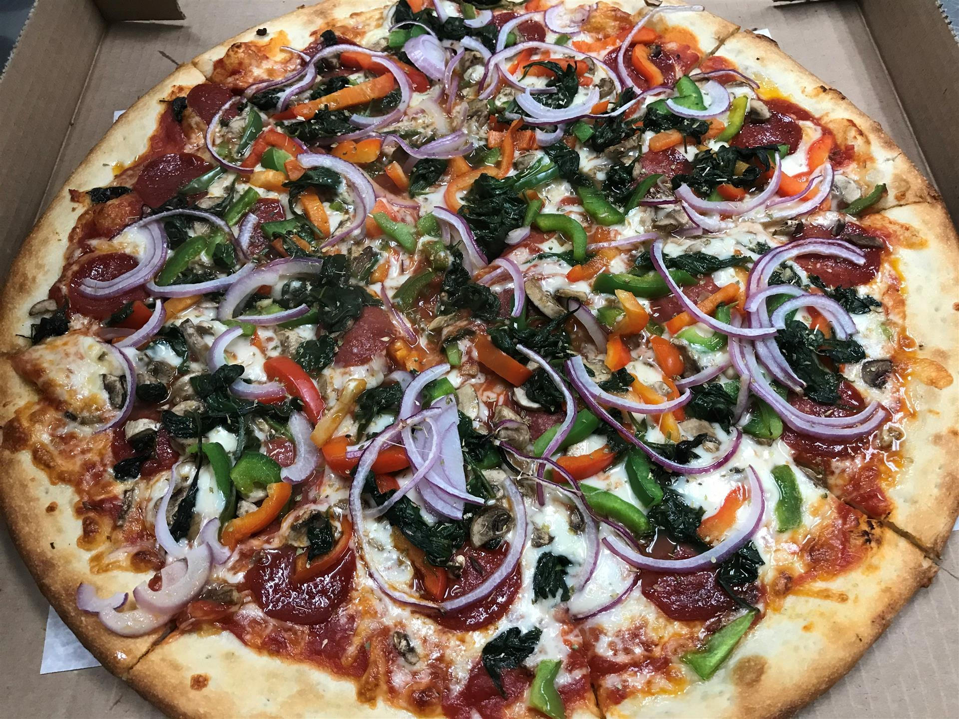 Veggie Lover's pizza. Red & green peppers, sautéed spinach, red onions & feta