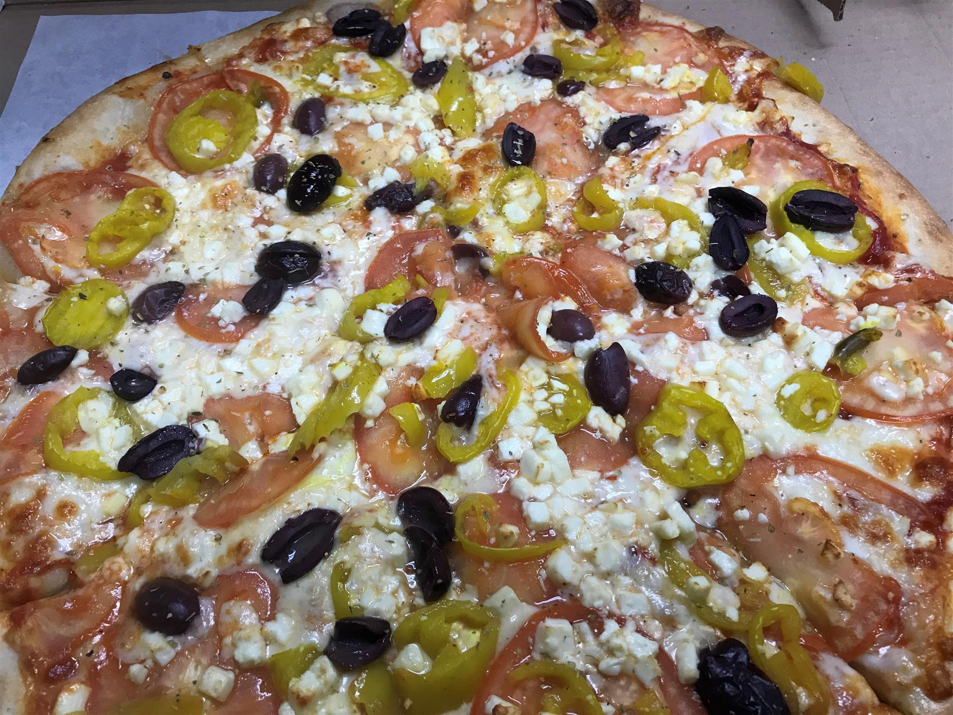 large pizza topped with tomatoes, banana peppers, black olives and feta cheese.