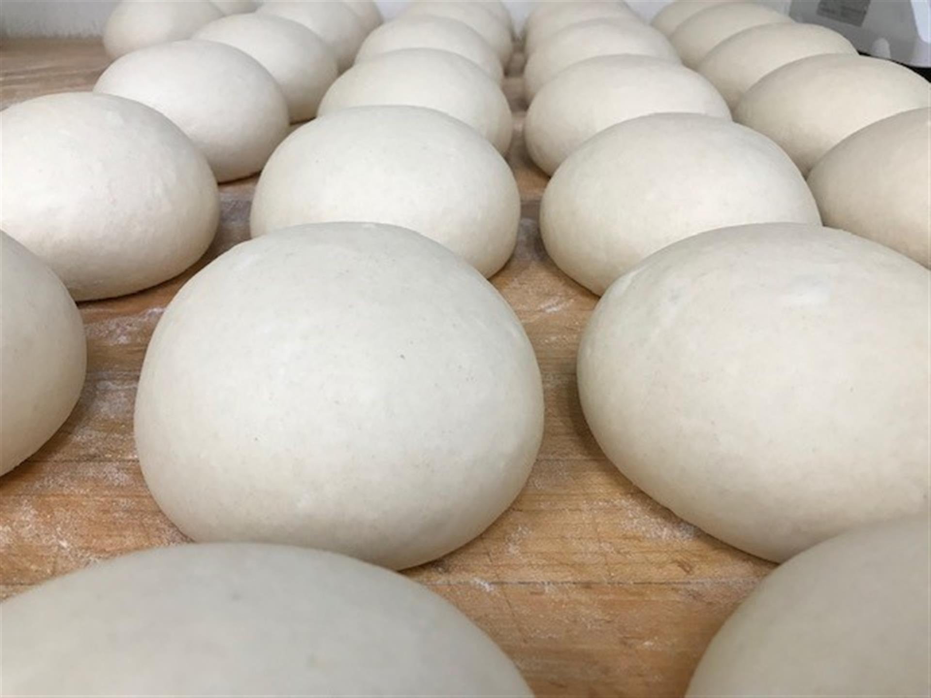 Pizza dough rolled into balls and lined up on wood cutting board.