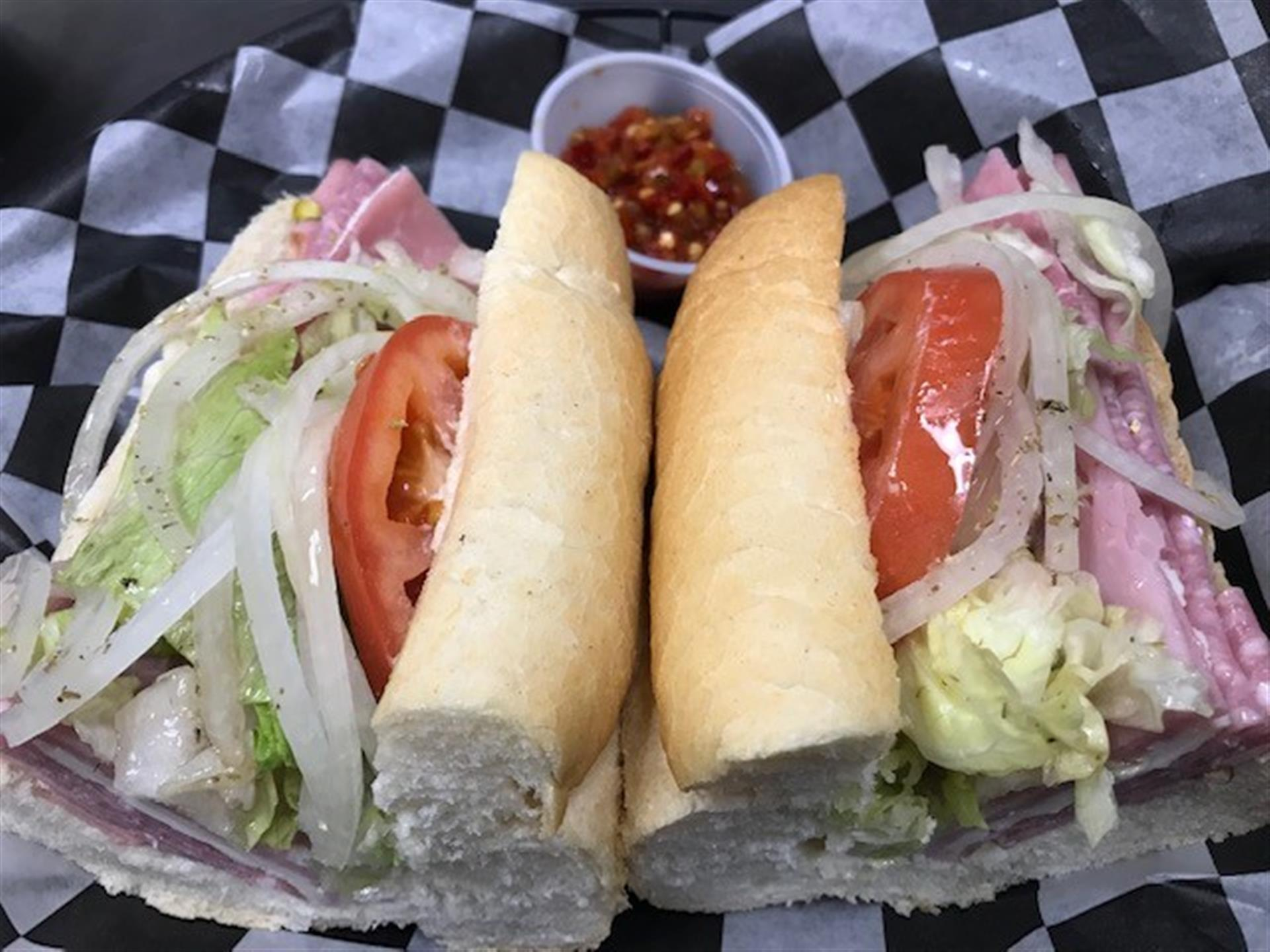 Ham & Provolone Sub. Deluxe ham, raw onions, mayo, lettuce, tomatoes & red hot peppers