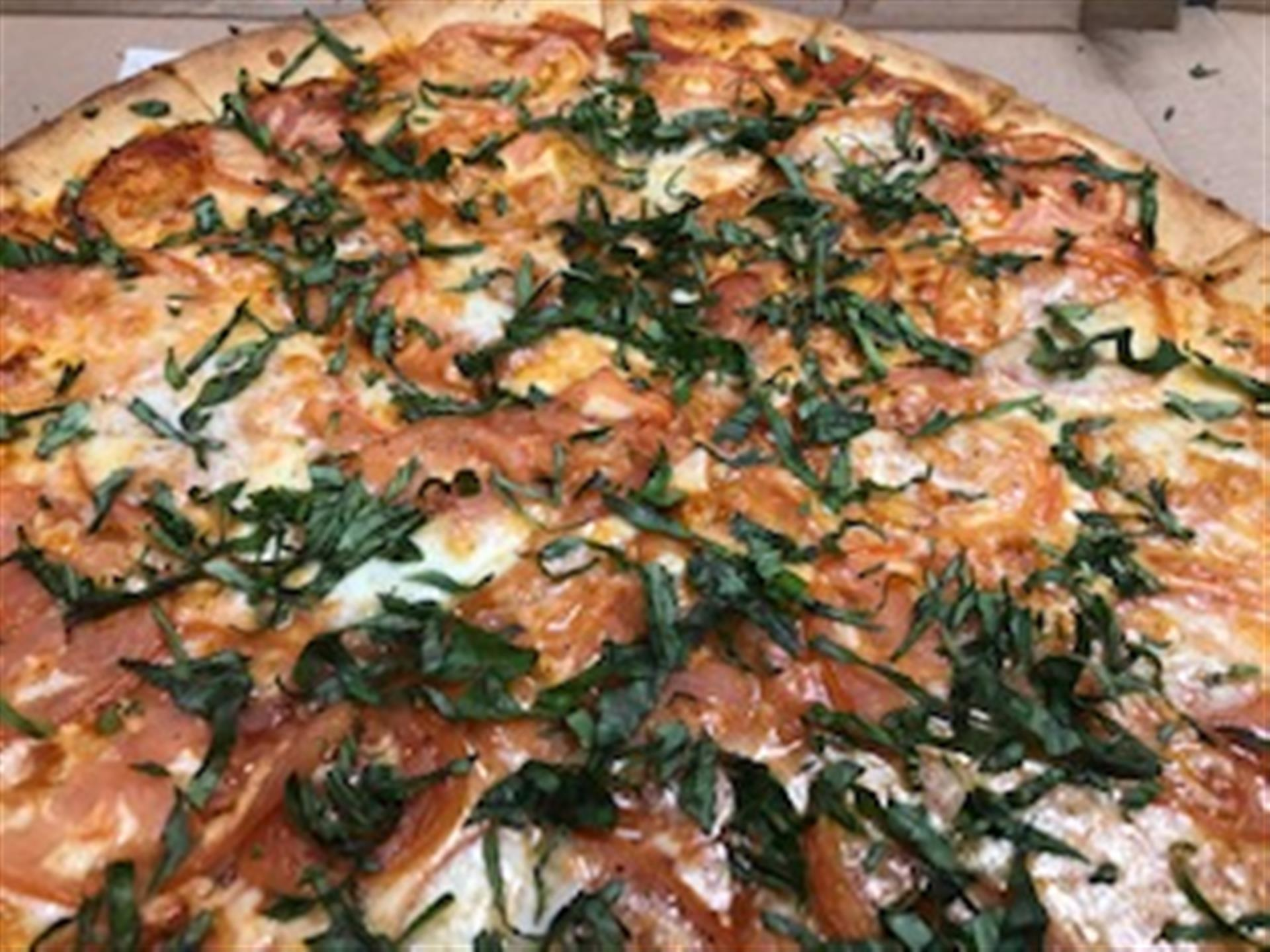 Margherita pizza close up. Light sauce, olive oil, fresh garlic, tomatoes, fresh basil, fresh mozzarella & seasonings