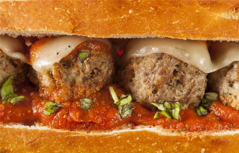 close up of a meatball sub with marinara and cheese.