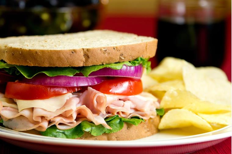 turkey sandwich with lettuce, tomato, and onion. chips on the side.