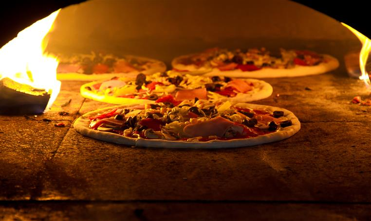 four pizzas with assorted toppings in the brick oven